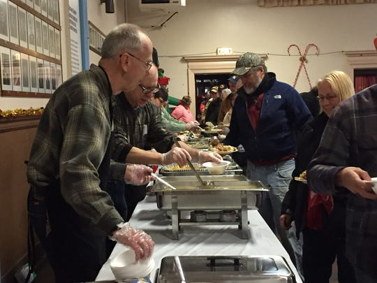 Volunteers dish up food options -- ham and pineapple, mashed potatoes, sweet potatoes, stuffing, gravy and more -- at the Bandera Family Christmas Dinner.