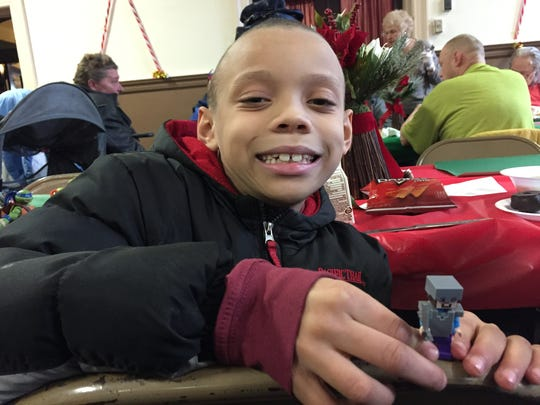 Jeremiah Mitchner, 7, plays with a Lego figure as he eats lunch at the Bandera Family Christmas Dinner.