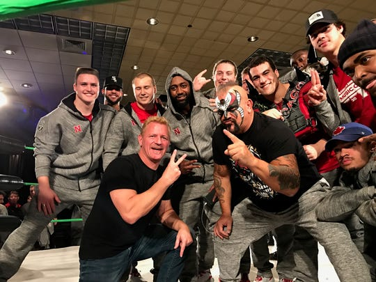 Members of the Nebraska football team pose for a photo with wrestlers during a private event at  the Renaissance Nashville ballroom on Wednesday night.