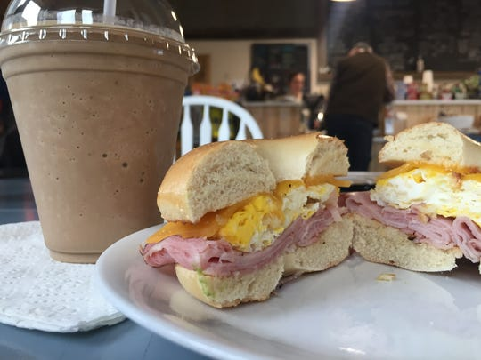 "A ham, egg and cheese bagel sandwich and ""monkey business"" coffee drink at Howling Cow Cafe."