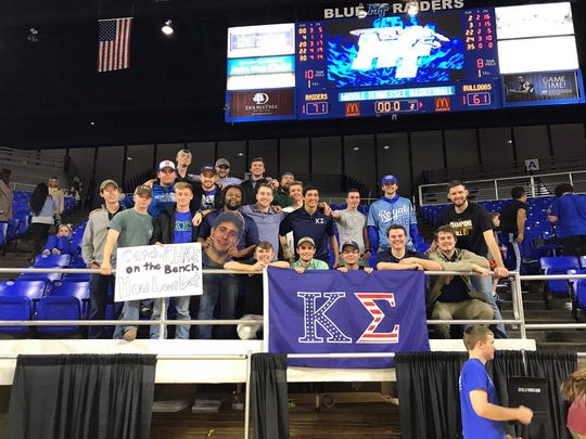 Members of the Kappa Sigma fraternity hold a sign and Fathead for MTSU point guard and fraternity brother Chase Miller.