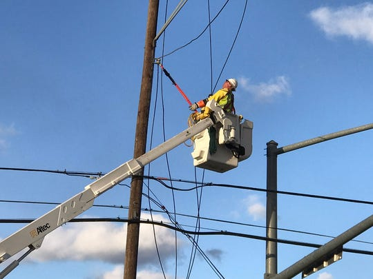 An electrician works to repair a utility pole after it was damaged by a tractor-trailer, resulting in traffic lights along a busy section of U.S. 30 in Guilford Township to go down at the start of the evening rush hour.
