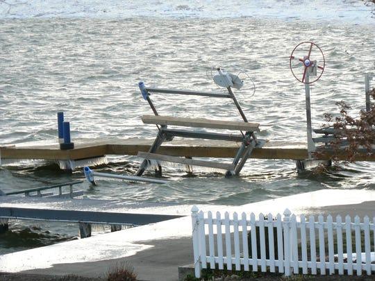 Wave-battered boat hoist and dock on Sodus Bay in Wayne County.