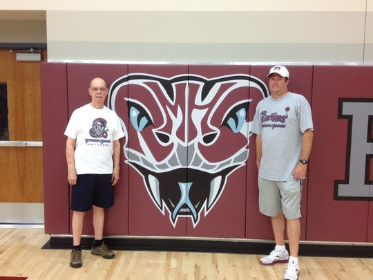 Larry Bennett (left) poses with head basketball coach Rob Hanmer next to the Rancho Mirage High School logo.