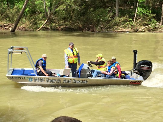Searchers motor upstream while looking for a paddler who was swept out of his canoe Wednesday on the flooded Buffalo River.