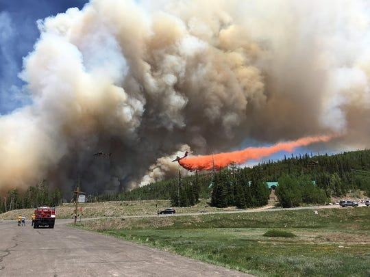 A tanker drops fire retardant on a wildfire burning