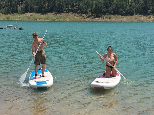 Two Wilderness campers try out paddle boarding on Grindstone Lake.