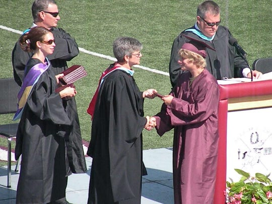 Adam Muzic receives his diploma from Owen High School