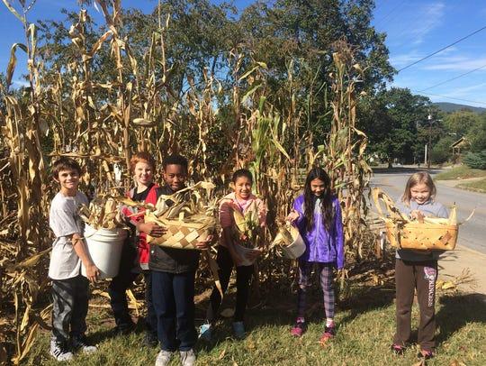 FEAST children harvesting corn in the fall.