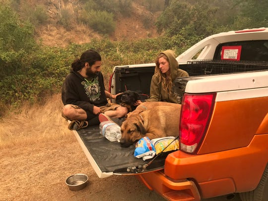 Thomas Reinheart and Sky Werner, three dogs and three cats wait by Highway 299 ready to leave if necessary on Thursday near the Helena Fire near Weaverville in Trinity County.