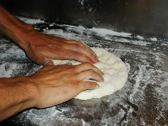 Pizza dough is worked by hand, ever-expanding the edges until it is 12 inches – a large serving for one person.