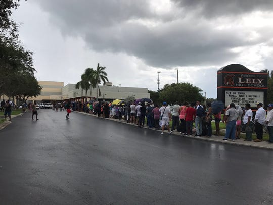 Hundreds wait outside Lely High School on Friday, hoping