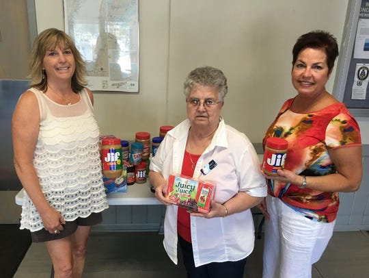 Barb Thill, center, accepts much needed Brown Bag Lunch