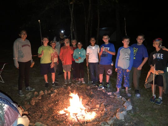Cub scouts around the camp fire at the cub family weekend at Wallwood Boy Scout Reservation in Quincy.
