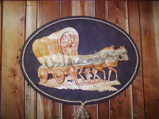 Décor includes this scene of a wagon and homesteaders