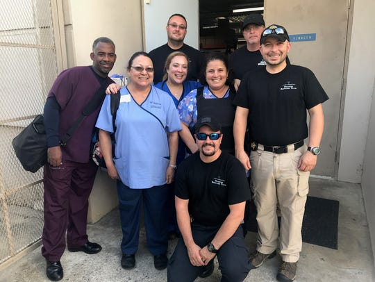 Adelaida Mier, in the solid light blue scrubs, stands amongst the other Fresenius Medical Care nurses who volunteered to go help in Puerto Rico and their security team.
