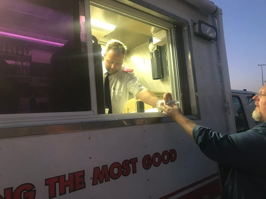 Capt. Patrick Gesner hands out doughnuts from the Salvation Army's emergency services vehicle. The truck is used to provide free food and drinks to areas impacted by natural disasters or other emergencies.