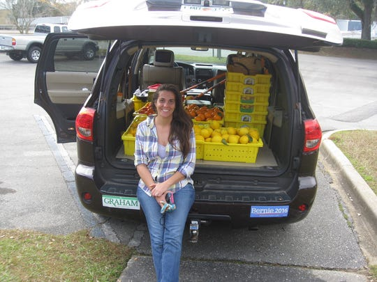 Tabitha Frazier with a harvest for the Leon Fruit and Nut Exchange.