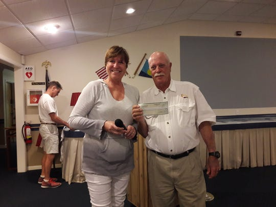Fort Pierce Yacht Club Commodore Janet Woodrow, left, presents a donation to Rivers Coalition speaker Jim Hart.