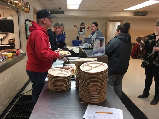 Jim Nault and Mike McKenna volunteering as servers Thursday at Salvation Army of Greater Green Bay during the charitable organization's Noon lunch hour. Many of those who visit the lunch hour also utilize the warming center in the organization's chapel.
