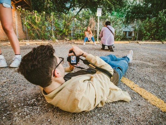 Will Roscher lies on the ground to take a photo of