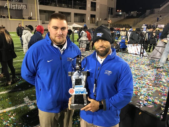 Former MTSU football strength coach Jason Spray hoists the Camellia Bowl trophy alongside his assistant, Lance Campbell, after the Blue Raiders defeated Arkansas State, 35-30, in Montgomery, Ala., on Dec. 16, 2017.