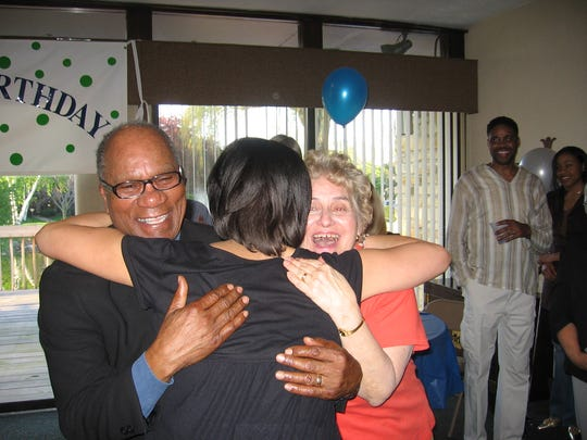 Robert Harris Jr. and his wife, Mary Ann, hug their daughter, Patrice Harris, during Robert's 80th birthday party.