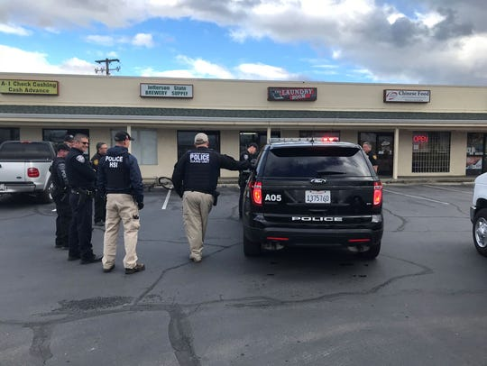 Anderson police and other local law enforcement officials confer outside a shopping center off Bruce Street during a March 1 sweep by the city's problem oriented police unit