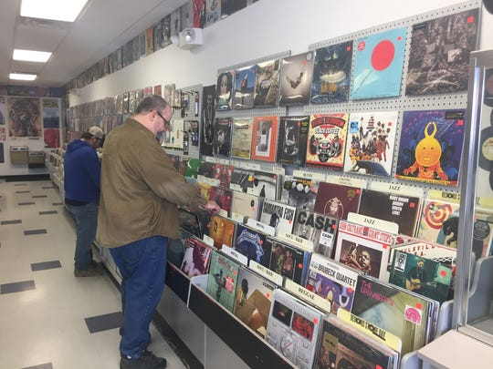 Customers are browsing through newly available vinyl records at Iko's Music Trade, located in the Village Acres Shopping Center in Springettsbury township.