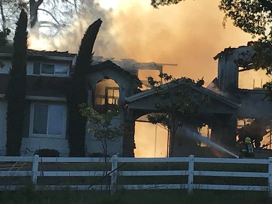 Firefighters battle a house fire in Bella Vista this