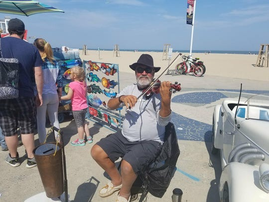 Lucian Ionescu poses with his violin on the Ocean City