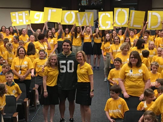 Blake Martinez (center) poses with G9 founder Annie Bartosz (left), her mother and G9 President Sarah Bartosz and CELA students and staff after an assembly honoring the school for raising more than $7,000 for childhood cancer research.