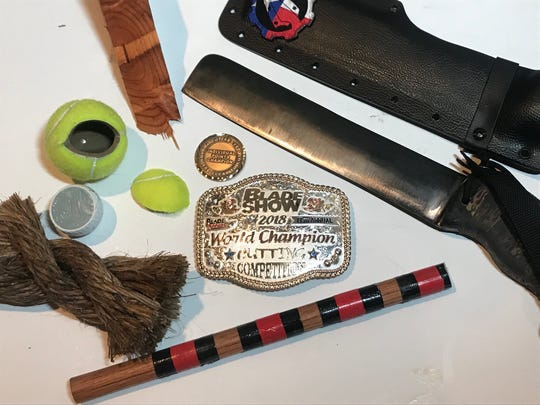For winning the world championship in cutting at the 2018 BLADE Show in Atlanta, Dwayne Unger received a custom belt buckle, displayed here along with his blade and items he chopped through to get the victory.