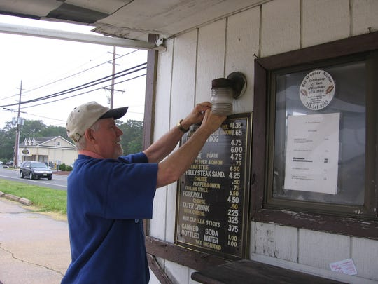 Gerald LaCrosse hanging a menu sign in 2009 on his hot dog stand, der Wunder Wiener.