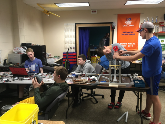 Students of FIRST 9956 work on their robot that threw out the first pitch at Miller Park June 15.