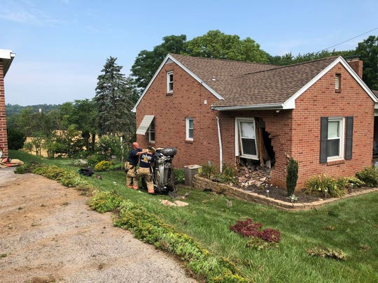 First responders flip an overturned car that crashed into this home on North George Street in Manchester Twp. on July 4, 2018.