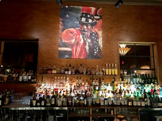 "A painting of Apollo Creed from ""Rocky"" behind the bar at Relief & Resource Co."