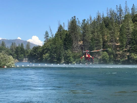 A helicopter dips into Whiskeytown Lake for water to