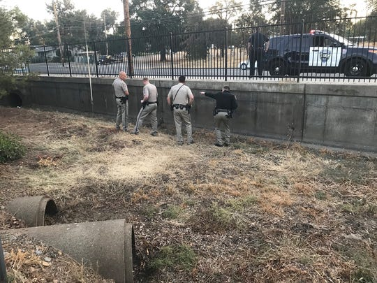 California Highway Patrol officers stand near a culvert on Churn Creek Road where they believe a bear went into after being spotted walking down the freeway on Monday, Sept. 17, 2018.