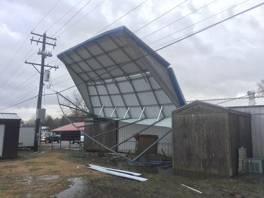 The Eagle building on U.S. 60 in Waverly. The roof of a large carport is resting against the powerlines. KU officials are on the scene (March 14, 2019)