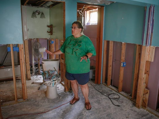 Leann Auxier shows the damage her basement sustained