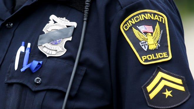 A Cincinnati Police officer waits in line for the visitation for Sonny Kim at Cintas Center on Thursday.