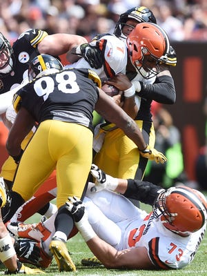 Cleveland Browns quarterback DeShone Kizer (7) is tackled by Pittsburgh Steelers inside linebacker Vince Williams (98) and inside linebacker Ryan Shazier (50) during the first half at FirstEnergy Stadium on Sunday.