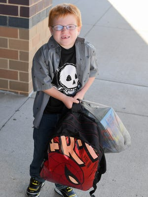 First-grader Connor Blanchard carries in his school supplies on Wednesday, Aug. 23, 2017, during the first day of school at Prairie Trail Elementary.