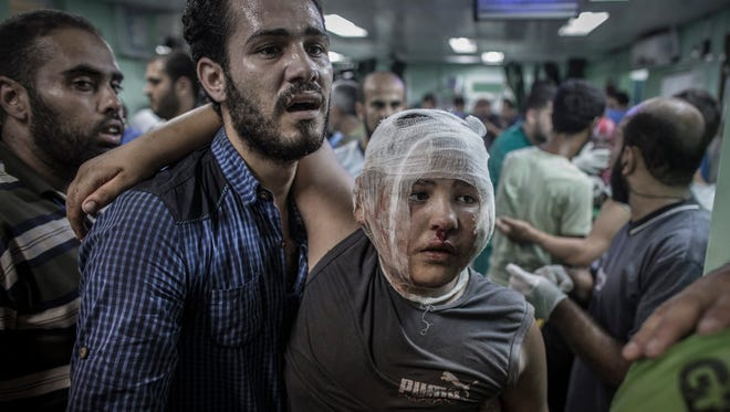 epa04328923 A Palestinian helps his son who got injured when a UN school for refugees was allegedly hit by an Israeli tank shell in the Kamal Adwan hospital in Beit Lahiya, Gaza Strip, 24 July 2014. At least 16 Palestinians were killed, among them seven children, and some 200 injured when an UN-operated school north of Gaza City was struck by Israeli tank shells, the Gaza Health Ministry said. Witnesses, who were in the school run by the United Nations for Relief and Work Agency (UNRWA), said Israeli tanks fired four shells at the school.  EPA/OLIVER WEIKEN ORG XMIT: GAZ009