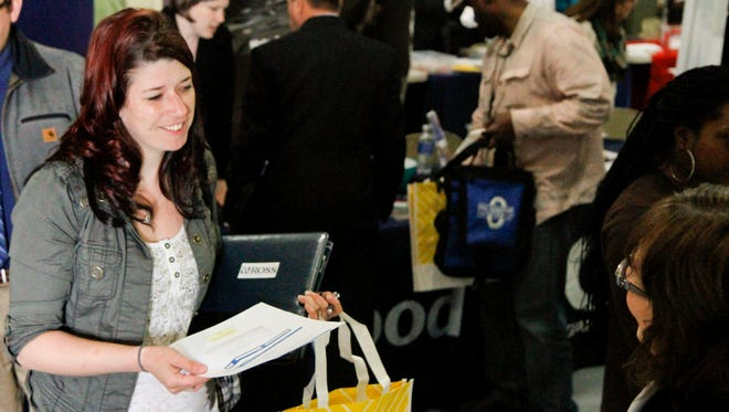 Jessica Bowen, left, talks with Sandra Modena, sales manager at Trillium Staffing, at the annual veterans job fair in May aboard the LST in downtown Muskegon, Mich. The Labor Department issued its report on job openings and labor turnover on Tuesday, Aug. 12, 2014.
