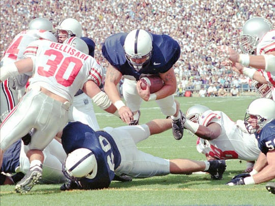 Penn State's Jon Witman (38) leaps into the end zone for a touchdown during a game in 1995. A year ago, Witman says he was in financial distress, severely depressed and hooked on painkillers, all of which led to a near-suicide attempt.