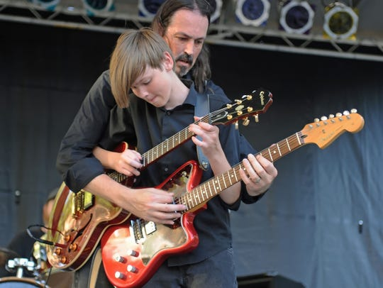 In this photo from the last Uptown Jazz & Blues, in July 2016, Jason Wells reaches around his son, Gibson, then 15, to play his son's Fender Tornado as Gibson takes over on his father's Epiphone. Wells will perform in July 2019 in a revived Star City Blues & Jazz Festival.