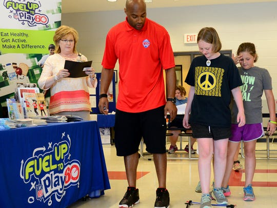 Former Tennessee Titan George Wilson gives Halee Flowers and Brianna Kuykendall instructions on how to run through a speed ladder, Thursday, June 1, during the Seamless Summer Meals Program kickoff at Trenton Elementary School.