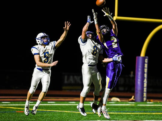 Northern Lebanon's Isiah Davila (8) and Stevie Herb (5) defend Lancaster Catholic's Philip Bomberger on the last play of the game as Northern Lebanon held off Lancaster Catholic 21-14 to win the Section 3 title at Lancaster Catholic on Friday, Nov. 3, 2017.